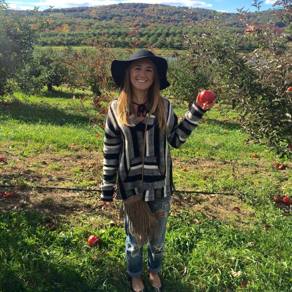 A woman picking apples and cider tasting at Weed Orchards and Winery