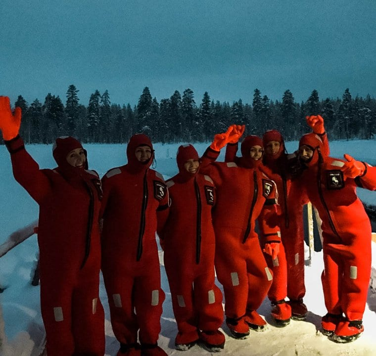 A group of cousins having fun in their wet suits during one of the most unique Lapland adventures