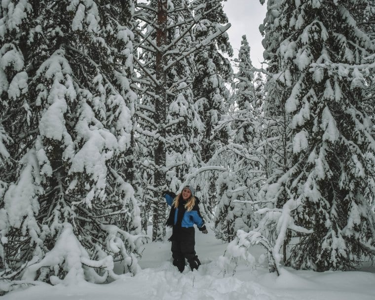 A happy woman in a snow filled forest