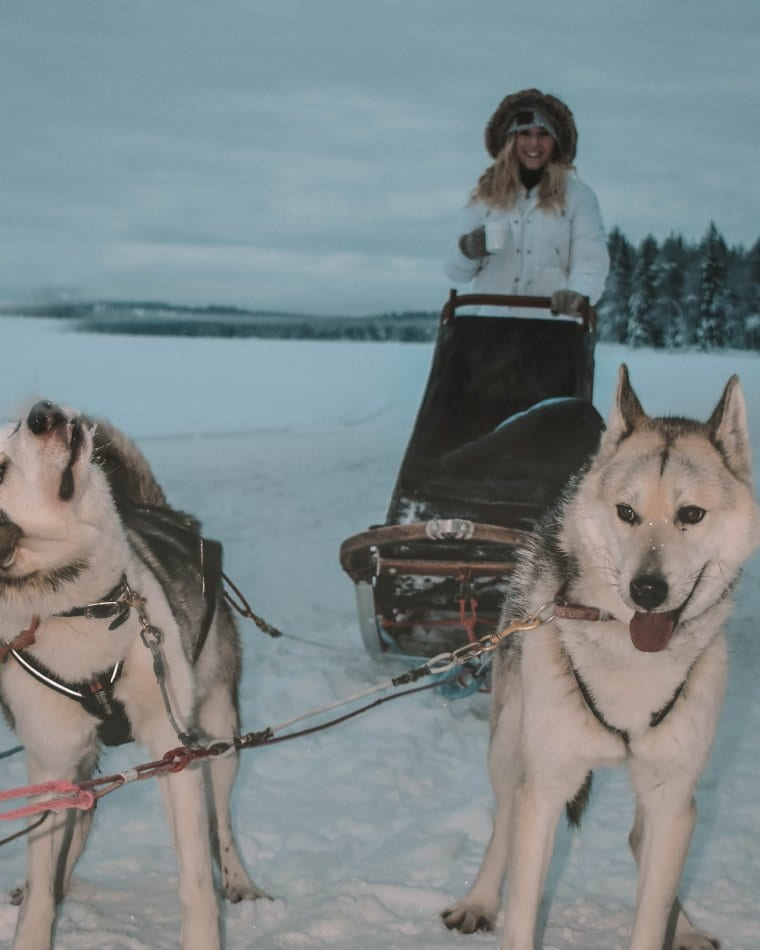 A woman on one of the best Lapland adventures, sleigh riding with huskies