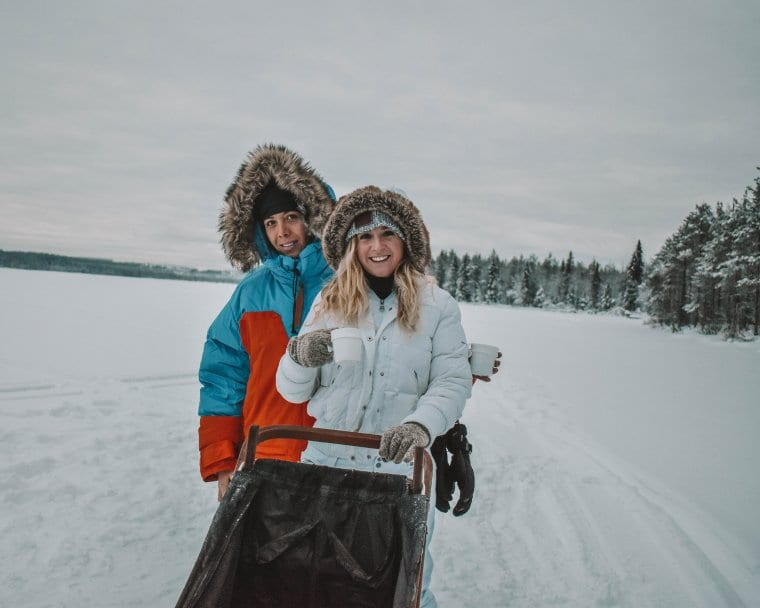 Two women enjoying glogi during fun adventures in Lapland