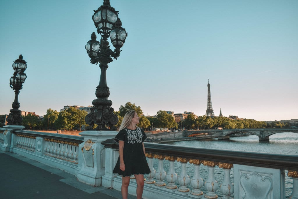 A woman looking at the Eiffel Tower during blue hour in Paris