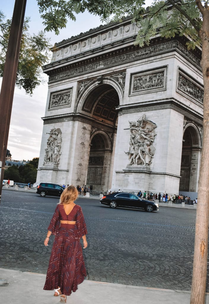 A woman looking at the Arc de Triomphe in Paris