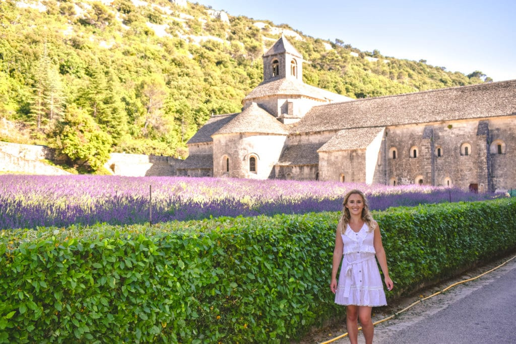 A woman standing by the lavender fields at the Abbaye Notre Dame de Senanque in France