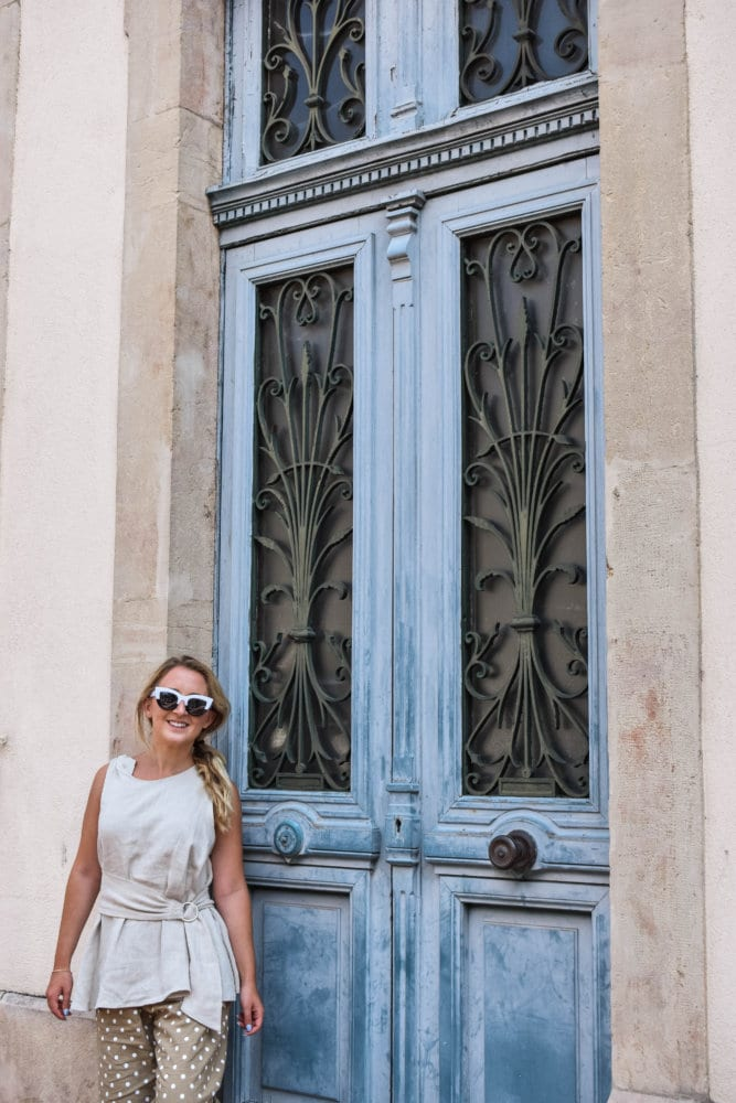 A happy woman in front of a beautiful door in Beaune