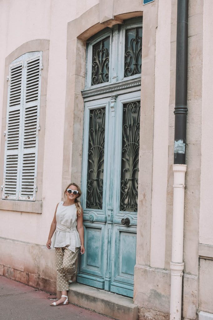 A woman enjoying her 10 days in France standing in front of a blue door in Beaune