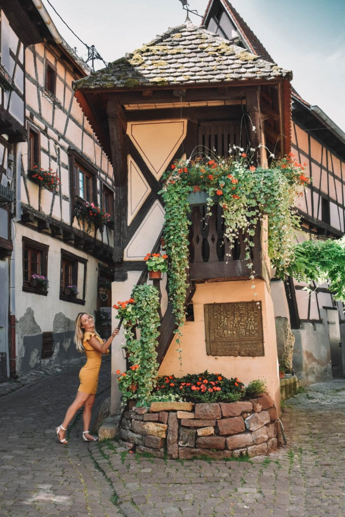 A woman standing in front of the Beauty and the Beast house in Eguisheim, France