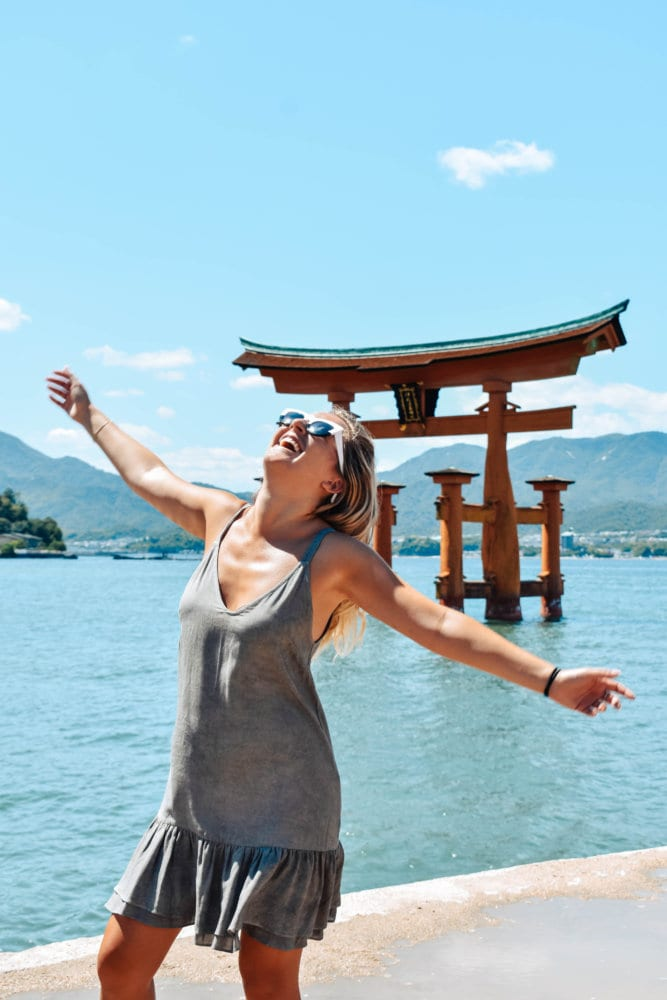 A happy woman standing in front of the floating tori gate in Miyajima