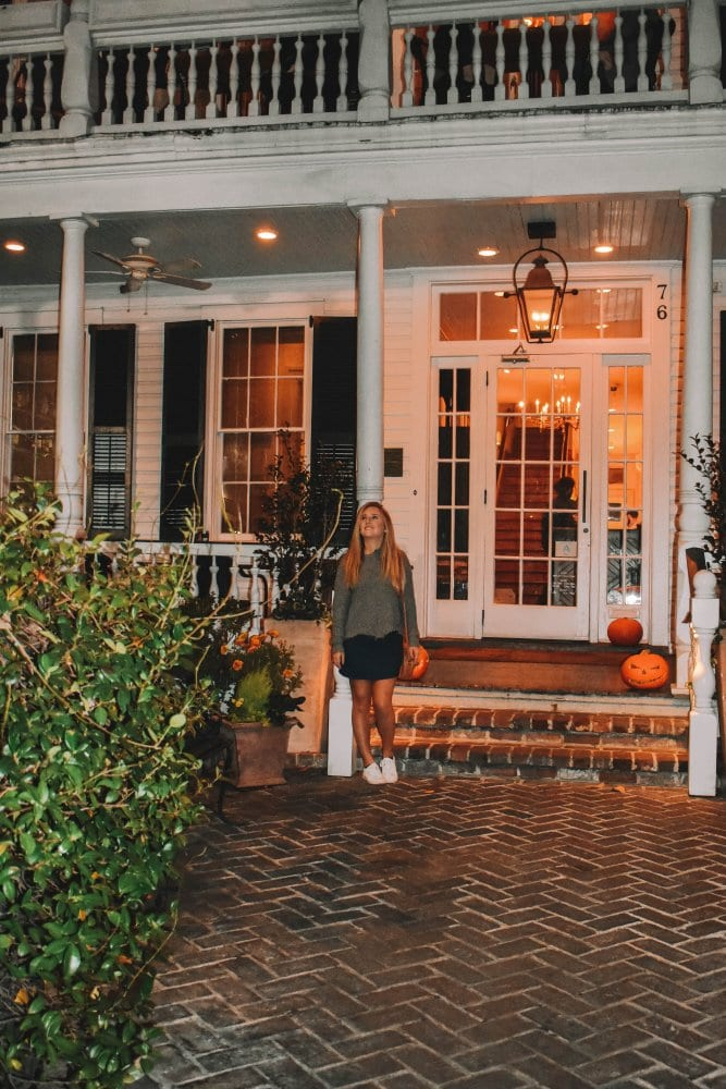 A woman outside of a restaurant in Charleston during the autumn season