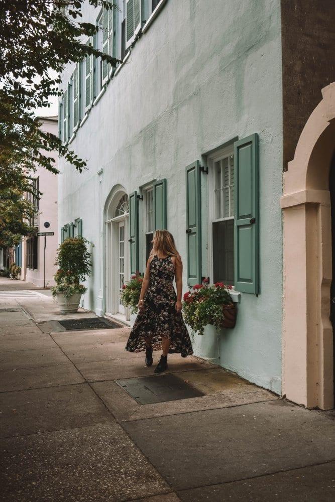 A woman wandering through Rainbow Row in Charleston