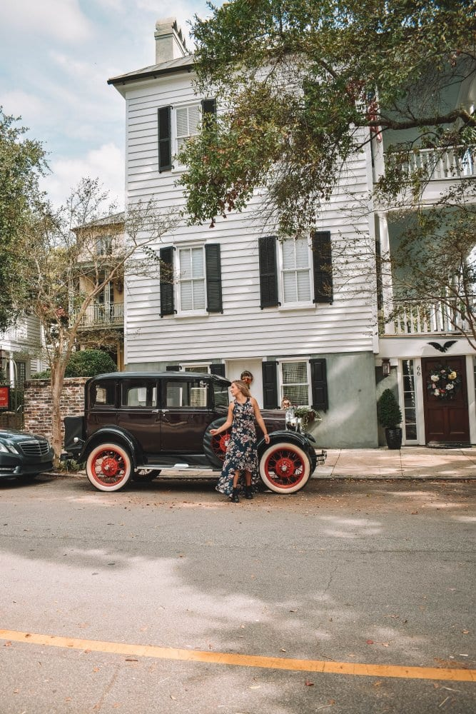 A woman in front of an authentic car in Charleston