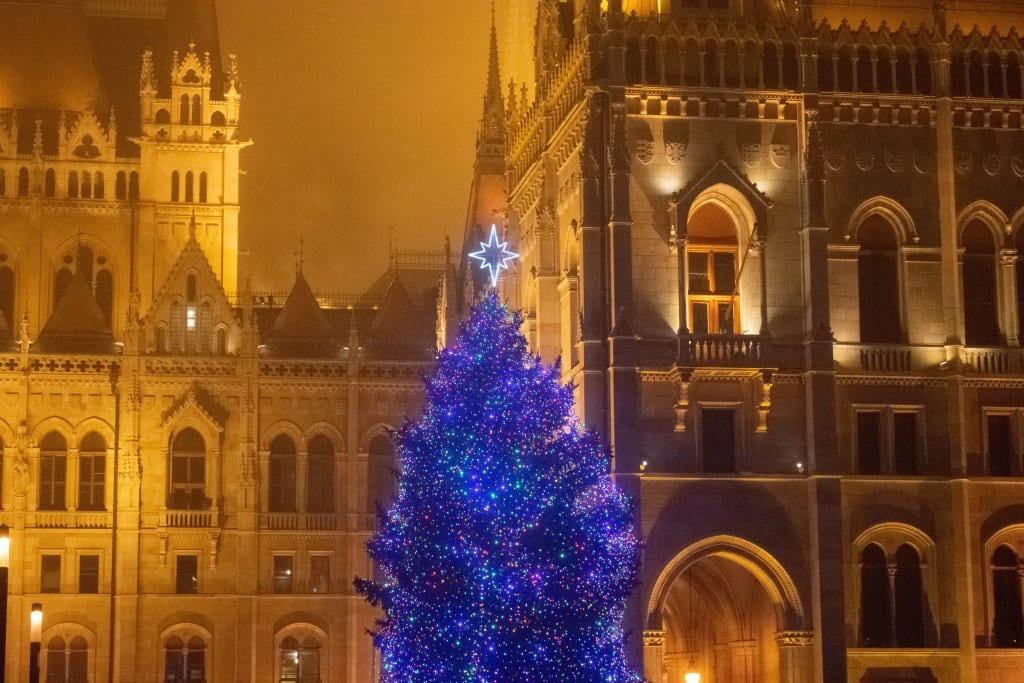 A lit up Christmas tree in front of the Budapest Parliament Building