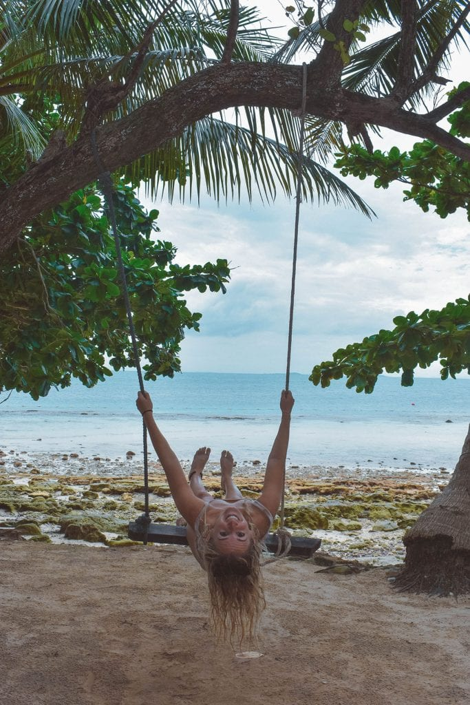 A woman having fun on the swings in Koh Samet, Thailand