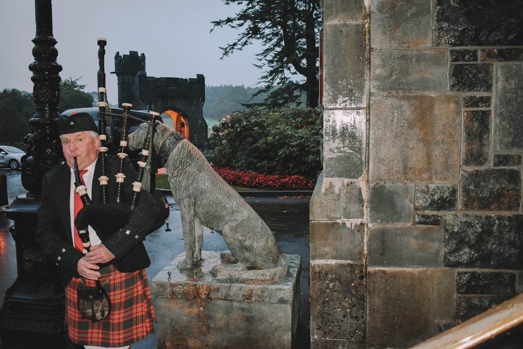 A man playing the bag pipe outside of Ashford Castle