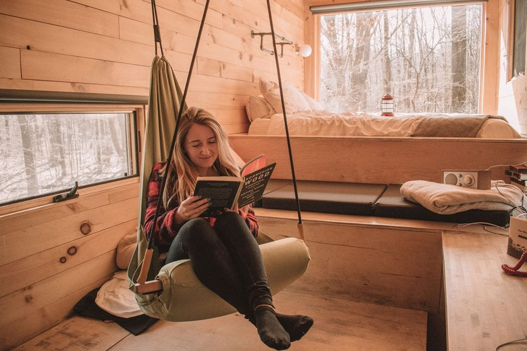 A woman reading a book on a hammock at a Getaway house in New York