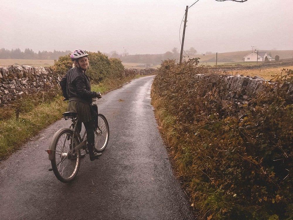 A woman riding a bike around rural Ireland