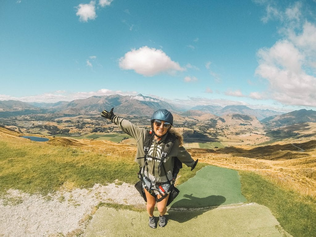 A woman enjoying her solo female travel adventure by paragliding in Queenstown
