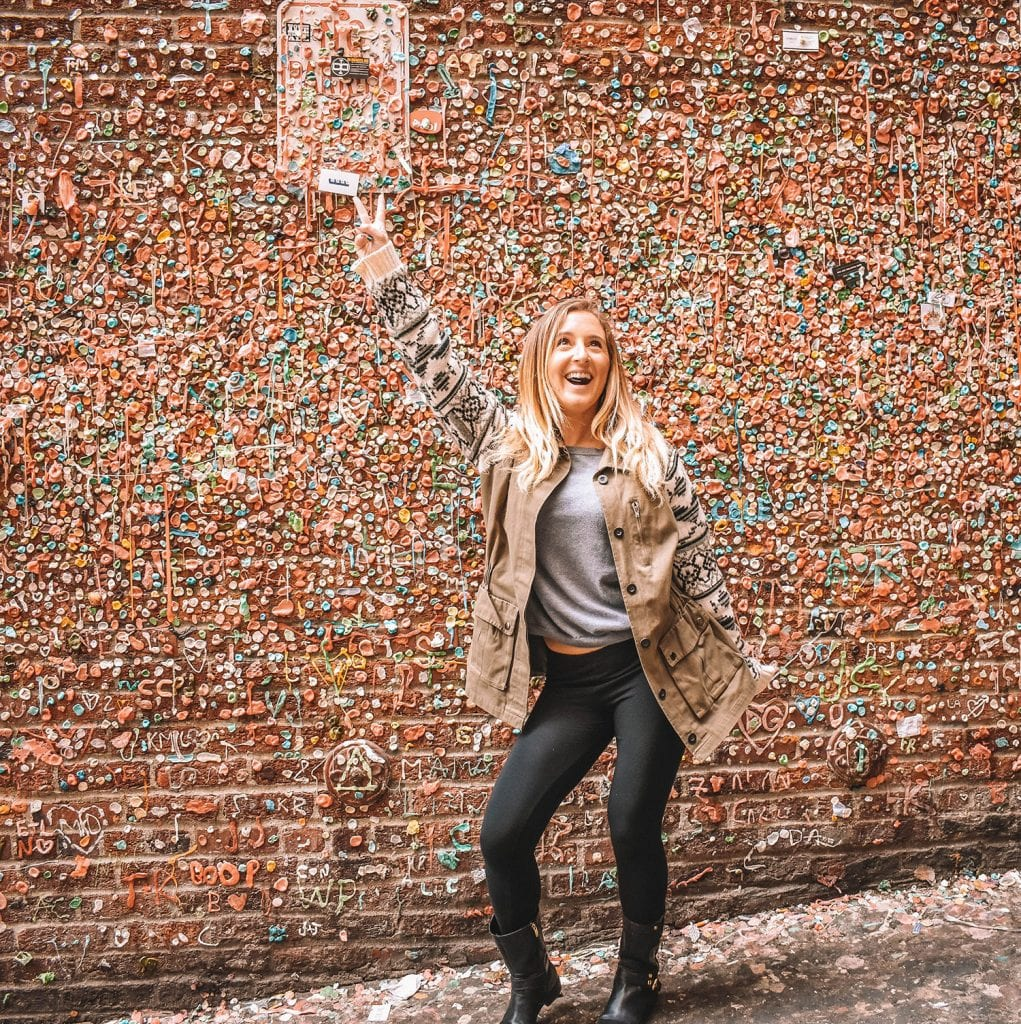 A happy woman standing in front of the gum wall in Seattle.