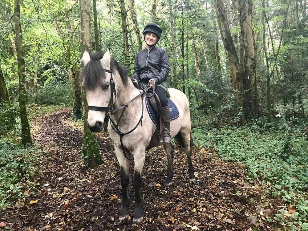 A woman horseback riding through the woods in Cong, Ireland