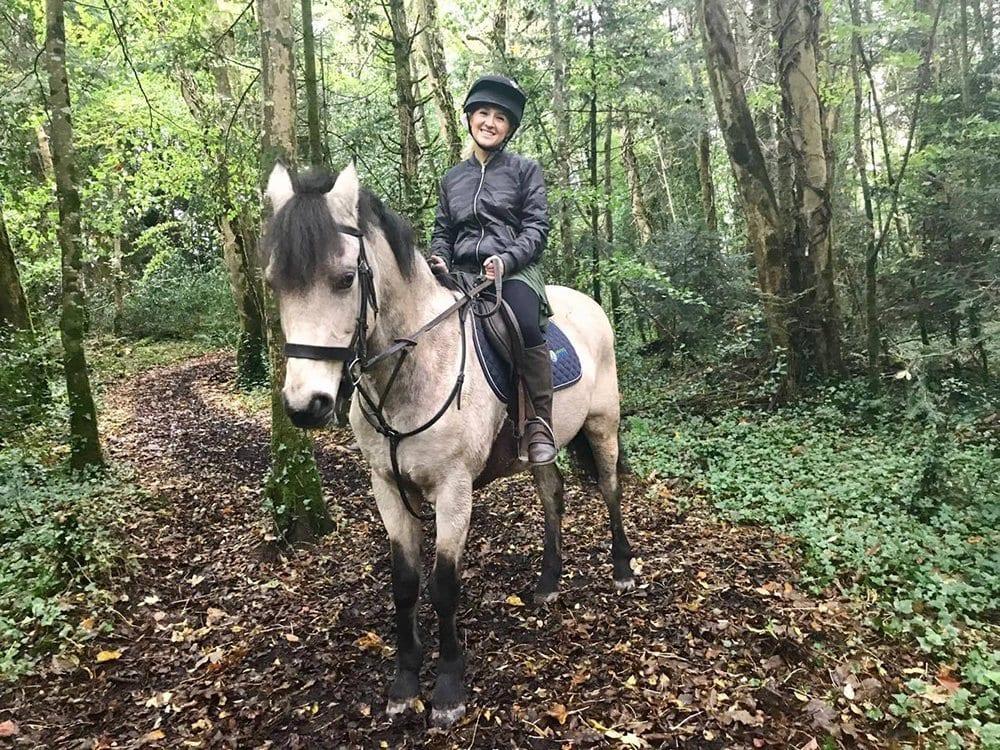 A woman horseback riding through the woods in Cong, Ireland