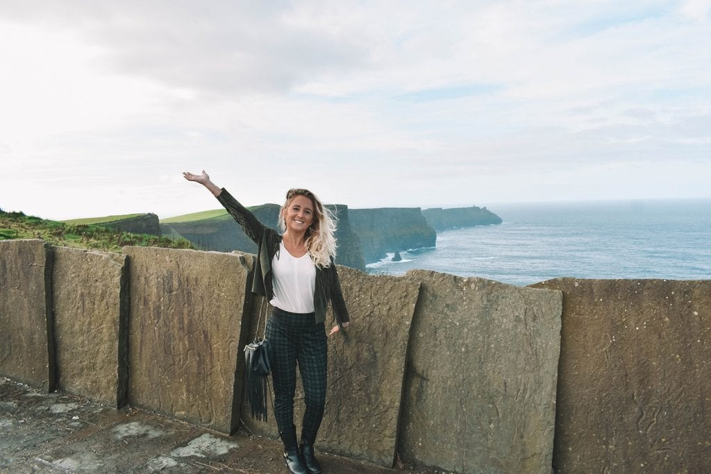 A happy woman at the Cliffs of Moher in Ireland