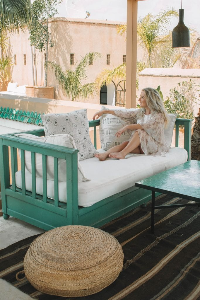 A woman enjoying a sunny day at a luxury riad in Morocco