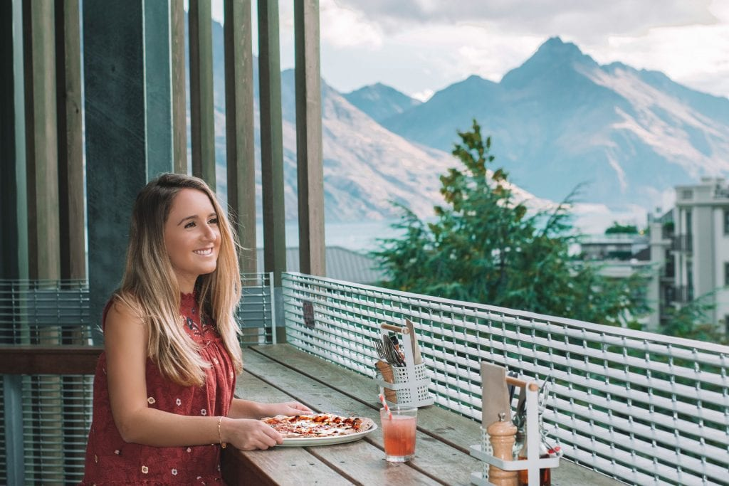 A young female eating pizza on a solo travel journey in Queenstown.
