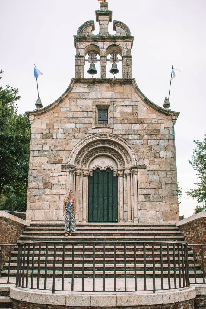 A woman standing in front of a small church in Northern Spain