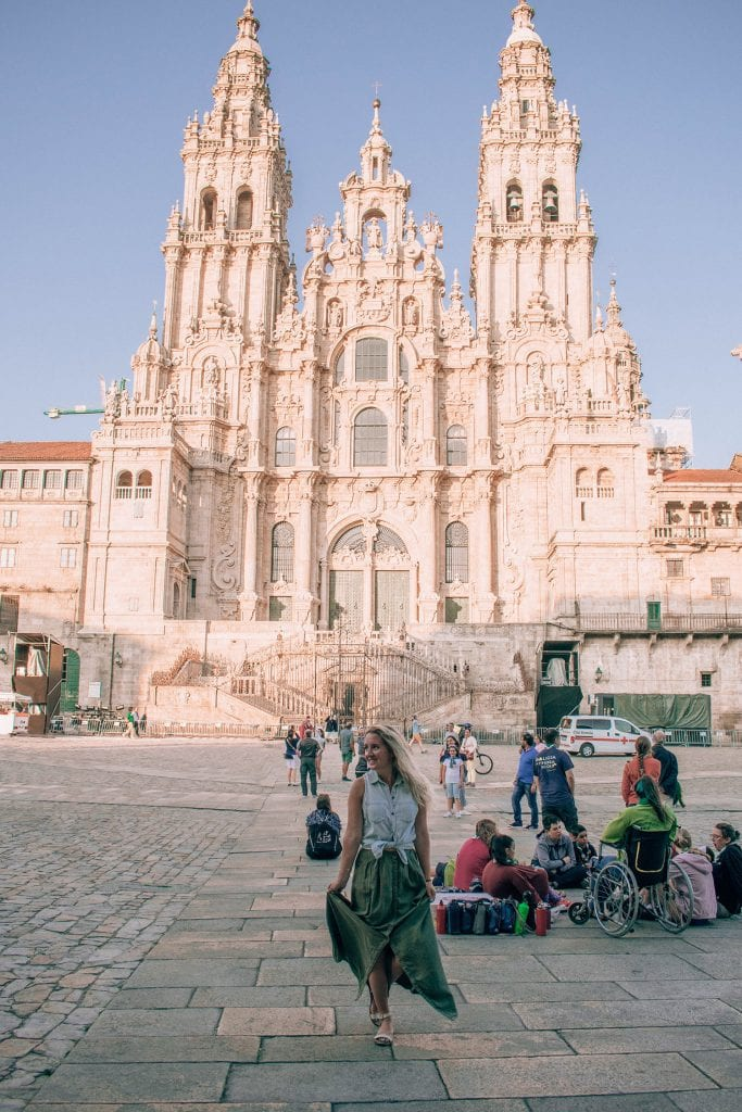 A woman standing in front of the Santiago de Compostela Cathedral happy to have completed the Camino de Santiago