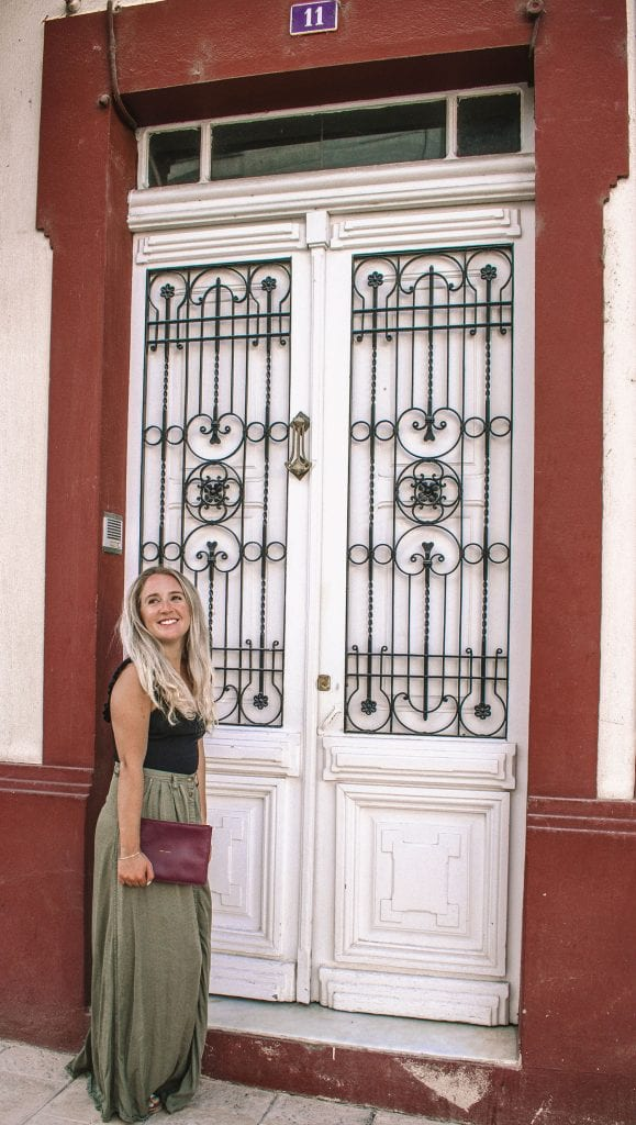 A woman in front of a decorative door in Sarria, Spain