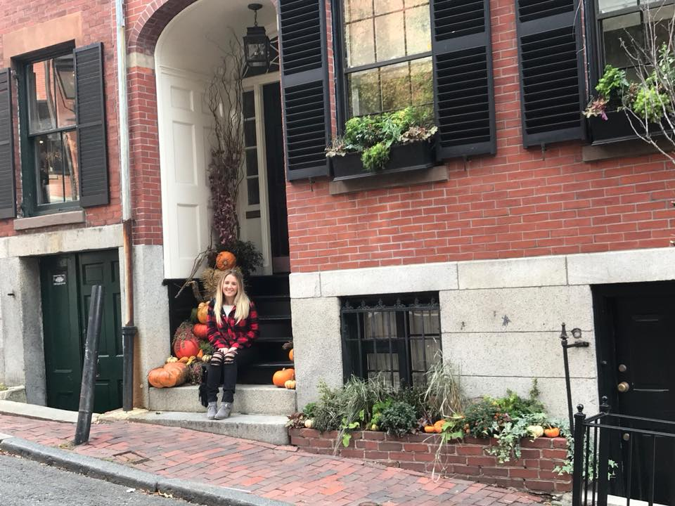 A woman sitting on a stoop in Beacon Hill during a girls weekend getaway in Boston