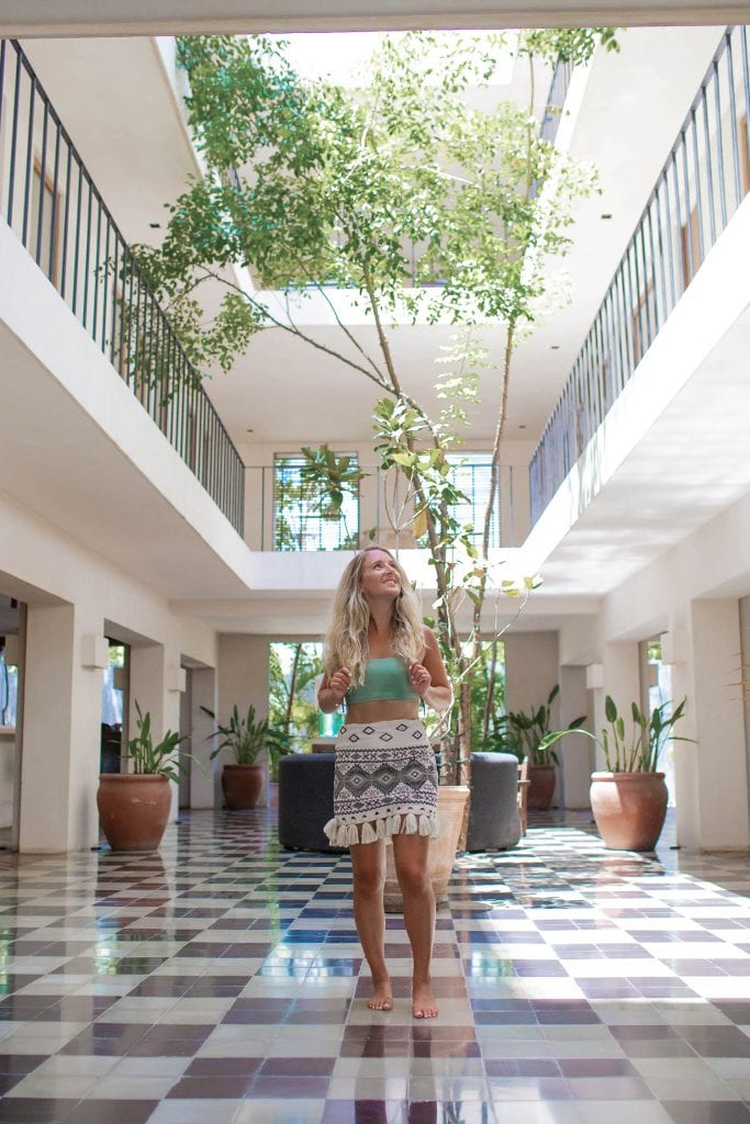 A woman in the lobby at Casa Pueblo boutique hotel in Tulum, Mexico