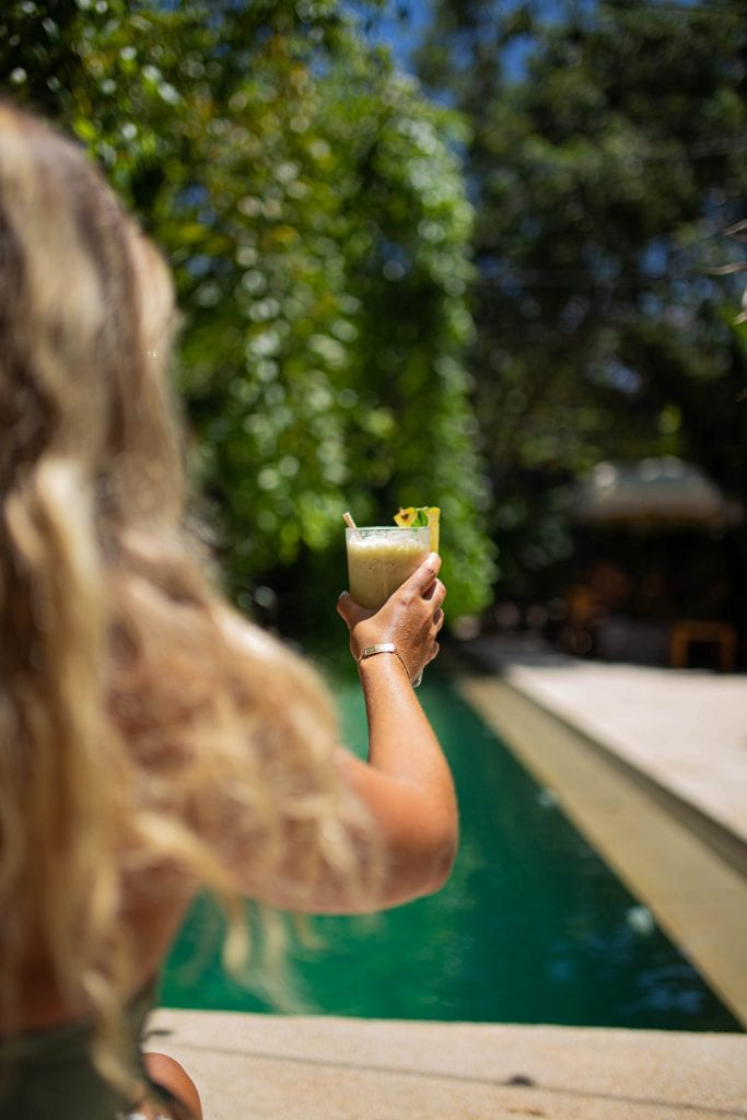 A woman holding a tropical smoothie at Casa Pueblo boutique hotel in Tulum