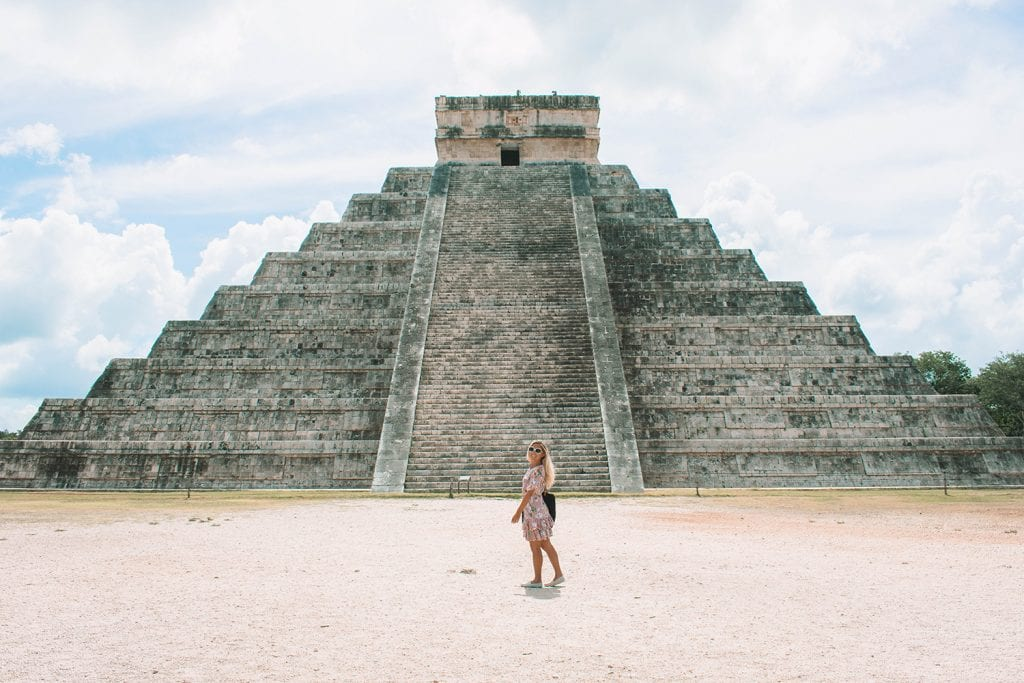 A woman walking in front of Chichen Itza in Mexico