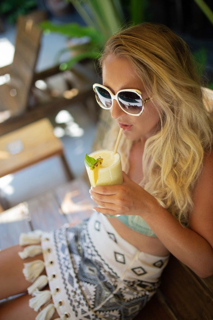 A woman enjoying a smoothie at Casa Pueblo boutique hotel in Tulum