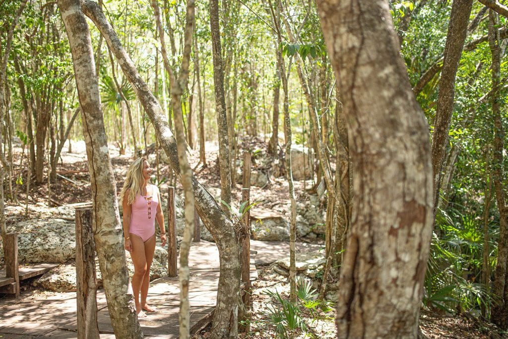 A woman walking through nature in Tulum, Mexico