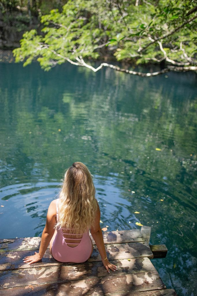 A woman enjoying the refreshing waters of Cenote Angelita
