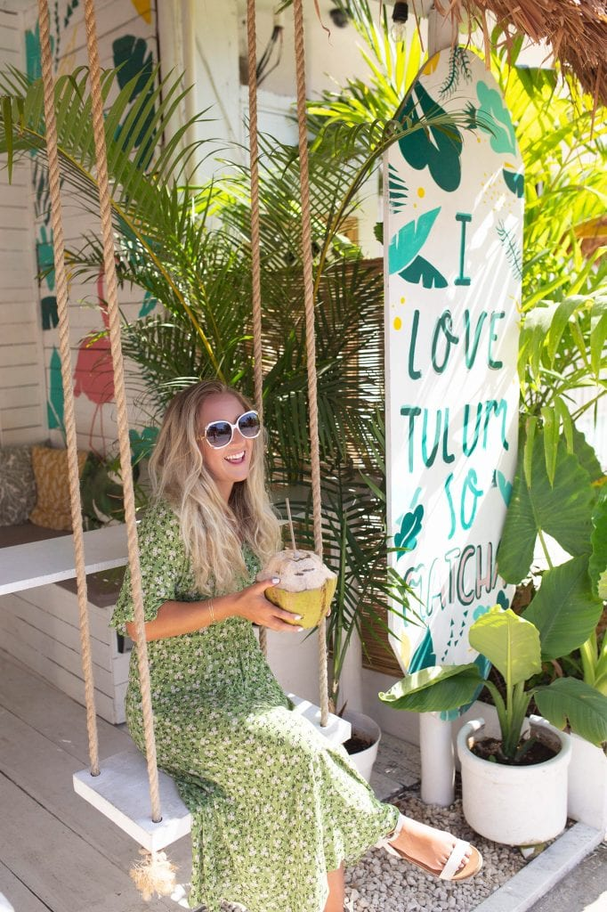A woman enjoying a coconut at Matcha Mama in Tulum