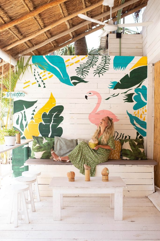 A woman laughing and enjoying a coconut at Matcha Mama in Tulum