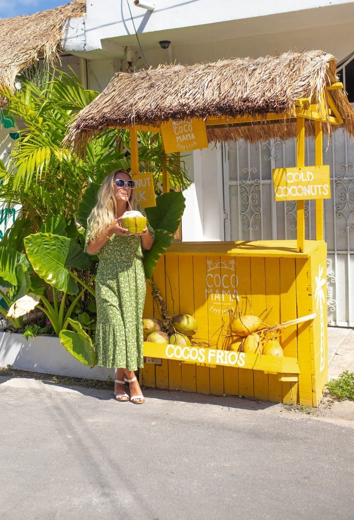 A woman drinking a coconut at Coco Mama in Tulum