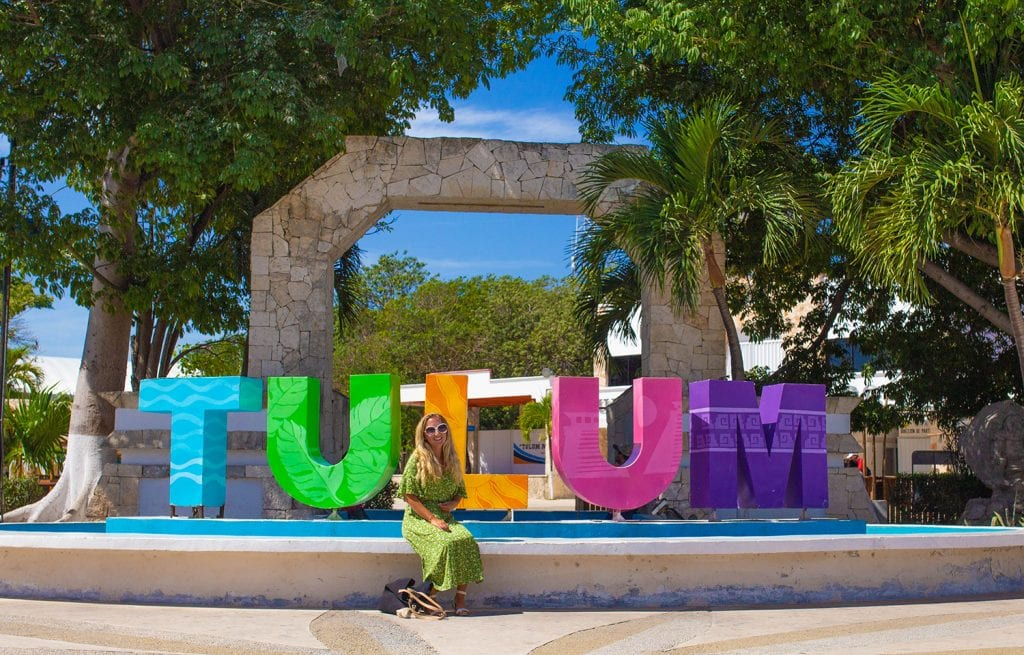 A woman sitting in front of a colorful Tulum sign in Mexico