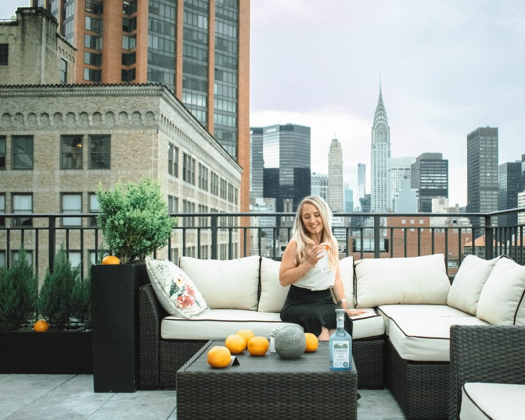 A woman enjoying a drink on a rooftop in New York City