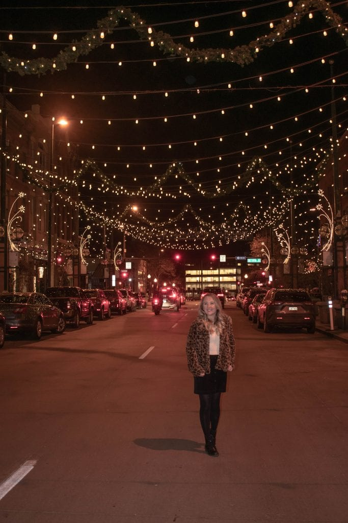 A woman standing in Larimer Square at night during winter