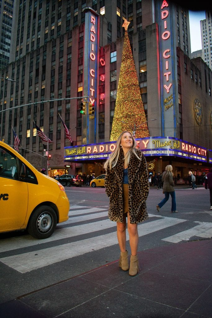 A woman in front of Radio City Music Hall during Christmastime in New York City