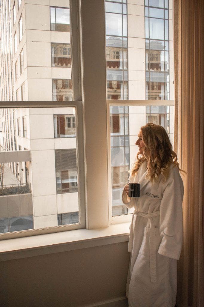 A woman having a cup of coffee at her hotel in Denver, Colorado