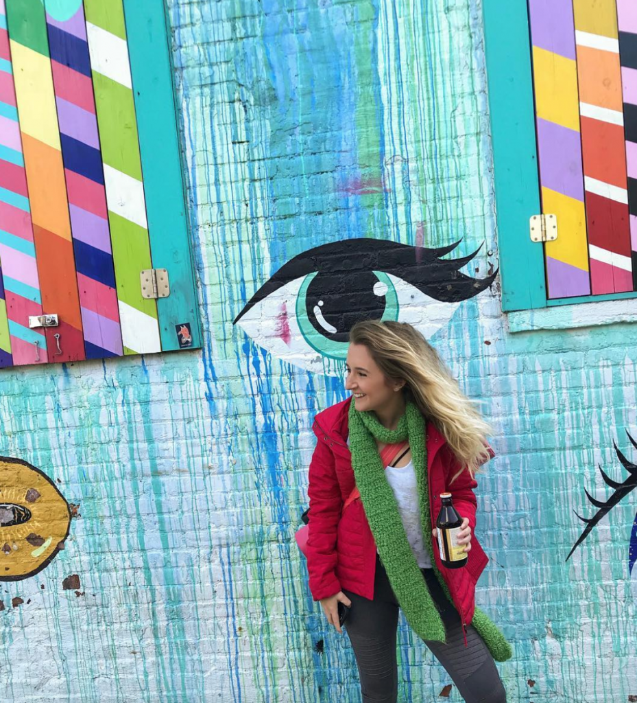 A woman in front of a colorful mural in Bushwick, Brooklyn in New York City