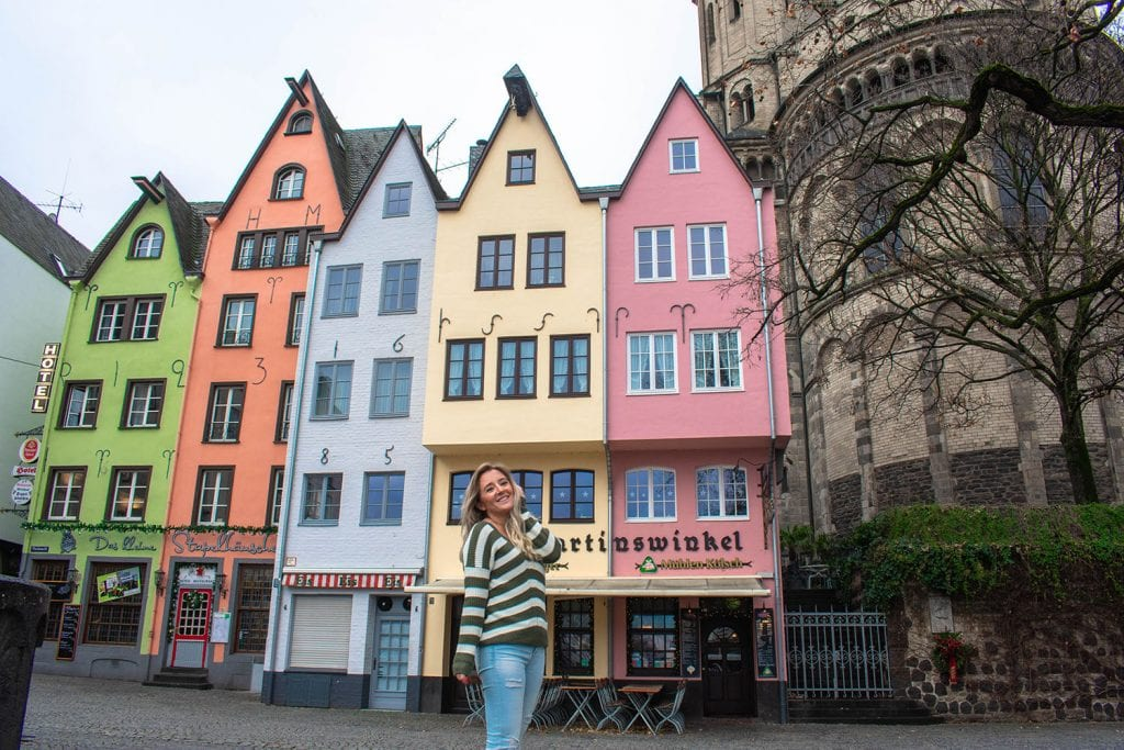 A woman standing in front of the colorful homes at the Fischmarkt in Germany