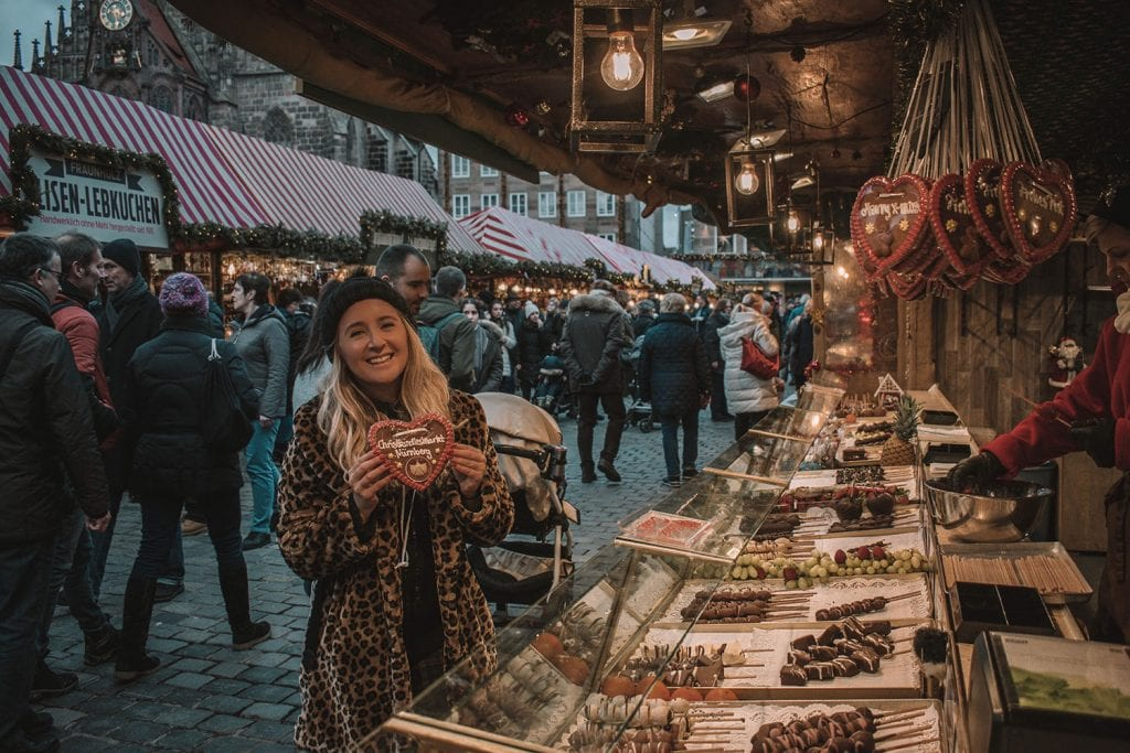 A woman purchasing a heart-shaped gingerbread cookie at a Christmas market stall in Nuremberg