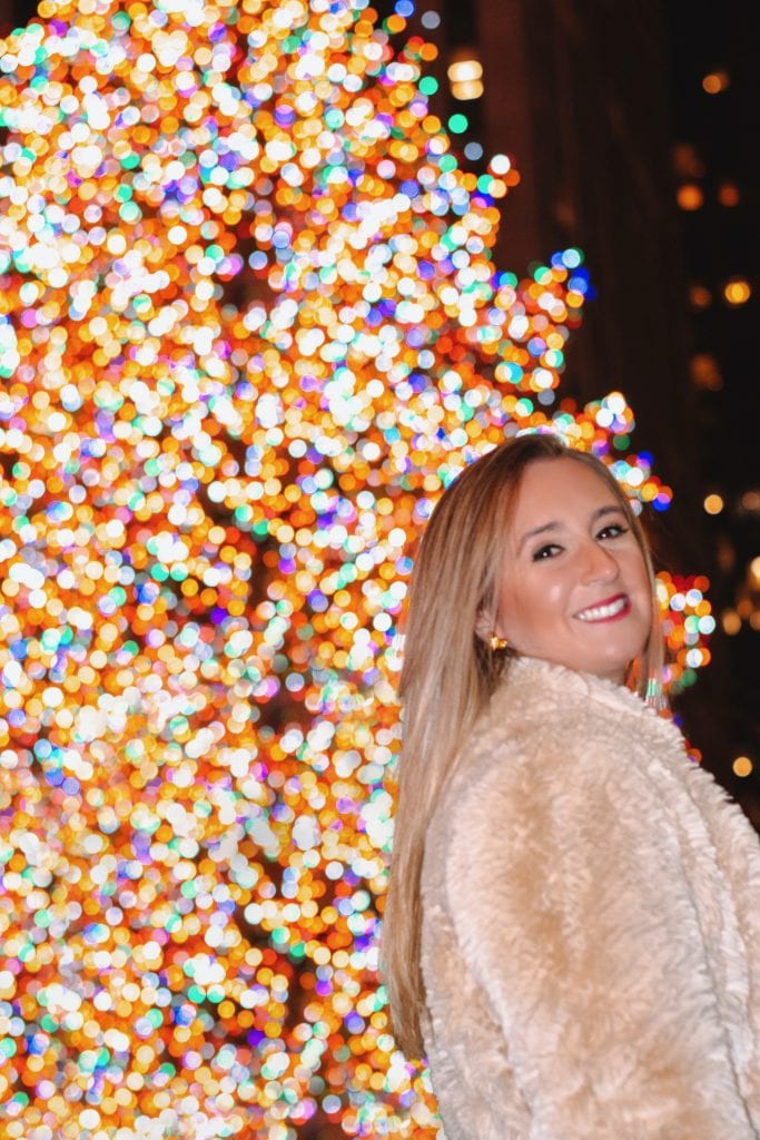 A woman in front of the Rockefeller Center tree in New York City