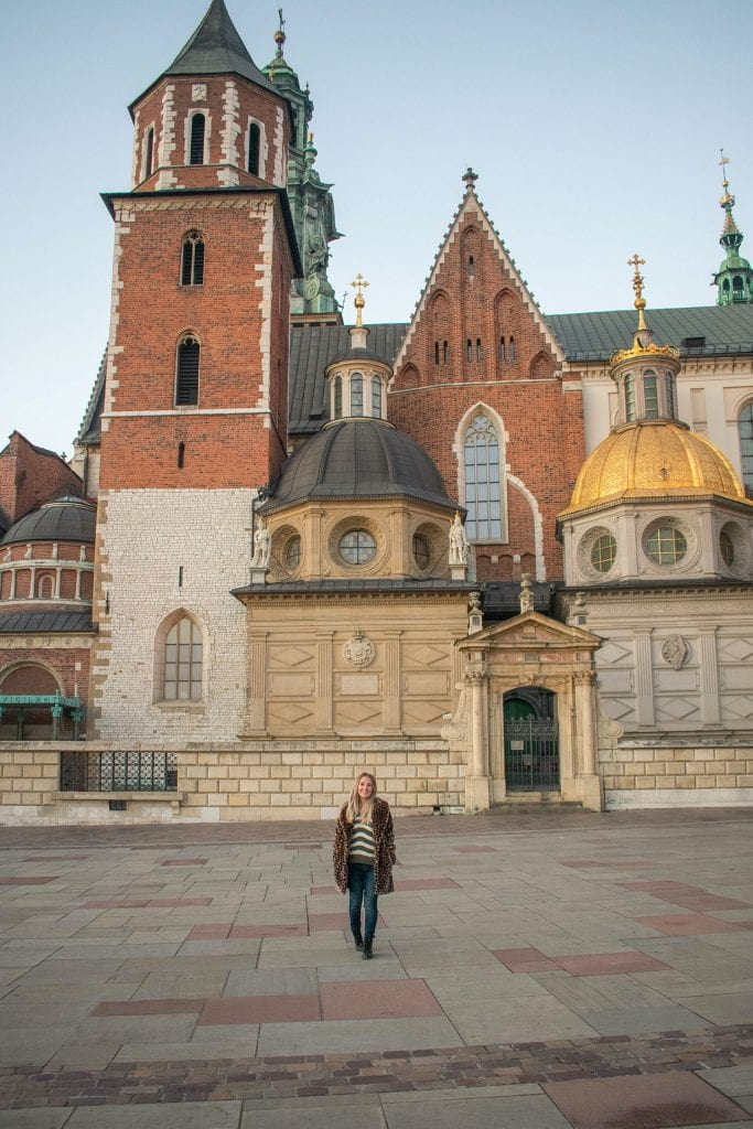 A woman standing in front of Wawel Castle in Krakow